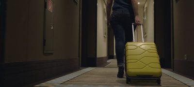 Mujer Viajera Con Maleta En El Pasillo Del Hotel. Ella Va A Registrarse O Salir Del Hotel